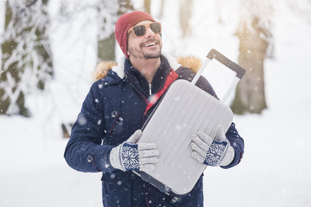 Portrait of young fashionable man on snow holding suitcase. Winter vacation travel concept.