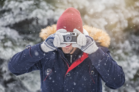 Fashionable man taking pictures with retro camera on snowy day. Winter vacation travel concept. 版權商用圖片