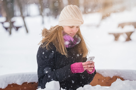Beautiful woman sitting on bench in the park and using smart phone winter landscape.