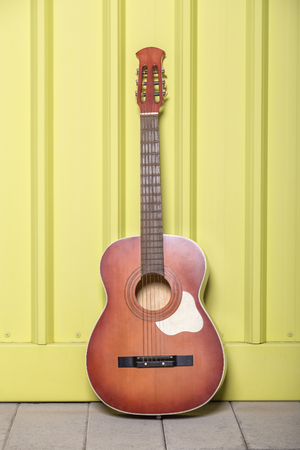 Acoustic guitar on yellow background.