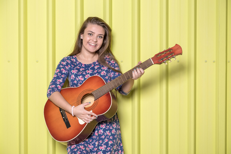 Beautiful teen girl with acoustic guitar isolated on yellow metal wall.