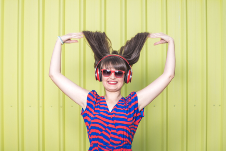 Happy woman with headphones enjoying her favorite song against yellow background. Reklamní fotografie