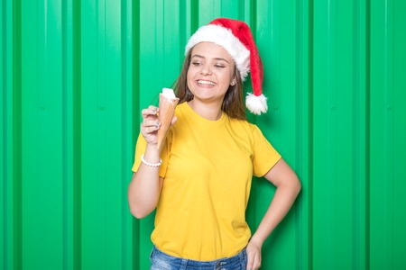Portrait of beautiful young woman wearing santa hat and holding ice cream in cone on green background.