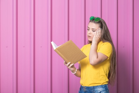 Stressed school girl holding a book on pastel pink background. Education concept. Space for copy. Reklamní fotografie