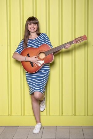 Young woman playing acoustic guitar on yellow background. Reklamní fotografie