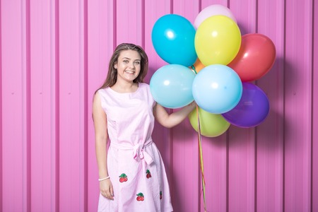 Beautiful young woman holding colorful balloons on pastel pink background.