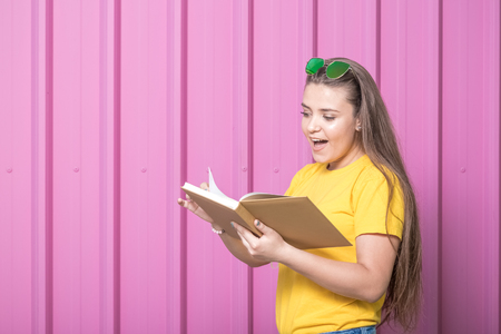 Beautiful young woman reading a book isolated on pastel pink background. Space for copy.