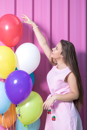 Beautiful young woman with balloons against pastel pink background. Reklamní fotografie
