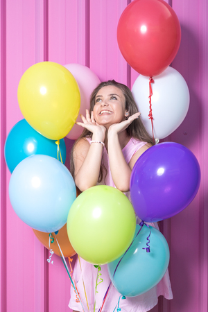 Beautiful young woman with colorful balloons on pastel pink background. Reklamní fotografie