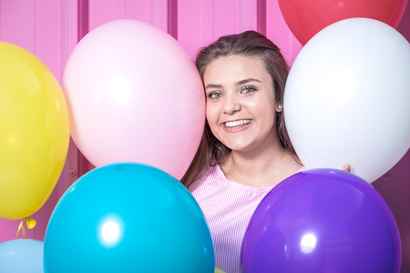 Close up portrait of beautiful young woman with colorful balloons.