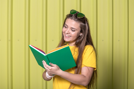 Portrait of a girl with a book against yellow metal wall background. Education concept.