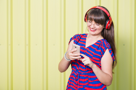 Portrait of beautiful woman with headphones using mobile phone on yellow background. Space for copy. Reklamní fotografie