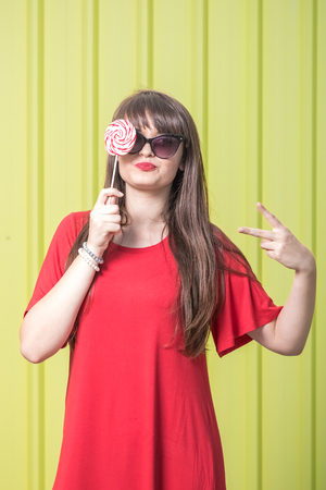 Cheerful girl with sunglasses in red dress covering her eye with lollipop candy against yellow background. Reklamní fotografie