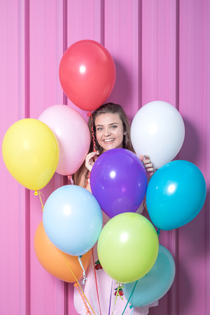 Portrait of beautiful young woman with colorful balloons on pastel pink background.