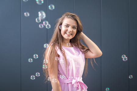 Portrait of beautiful young girl with soap bubbles against gray background. Reklamní fotografie