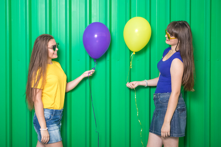 Two friends with balloons against green background. Reklamní fotografie