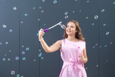 Beautiful young girl playing with soap bubbles against gray background. Reklamní fotografie