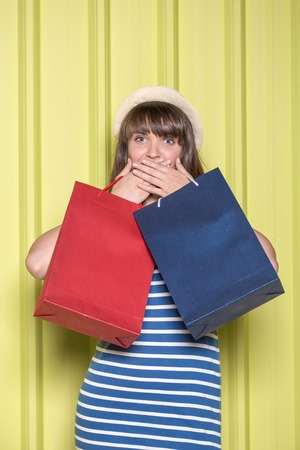 Portrait of an excited girl with hands over her mouth holding shopping bags. Sale surprise concept.