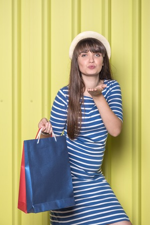 Portrait of beautiful woman with shopping bags against metal wall.