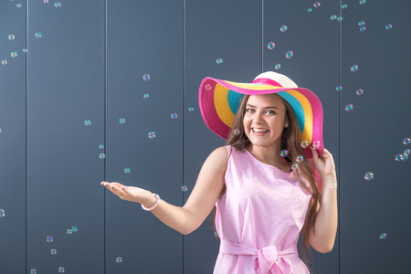 Portrait of beautiful young girl with sunhat and soap bubbles against gray background.