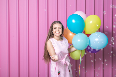 Portrait of beautiful young woman with colorful balloons and soap bubbles on pastel pink background.