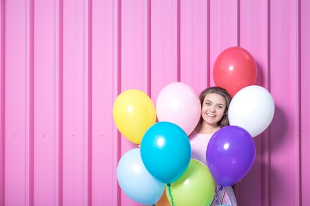 Portrait of beautiful young woman with colorful balloons on pastel pink background. Space for copy.