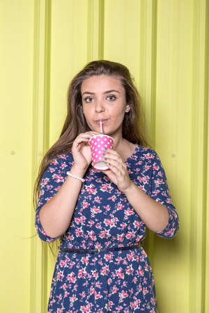 Portrait of cute girl drinking juice from paper cup with drinking straw polka design isolated on yellow background.