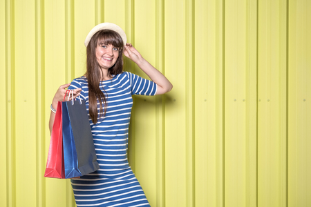 Portrait of happy girl in sun hat holding shopping bags on yellow background. Summer shopping concept. Space for copy. Reklamní fotografie