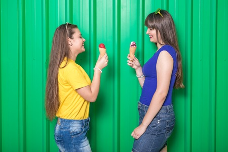 Two beautiful young girls eating ice cream against green background. Fashion and summer concept.