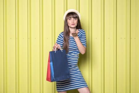 Young girl sending kisses and holding shopping bags on yellow background. Summer shopping concept.