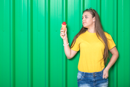 Beautiful fashionable girl holding ice cream against green background.