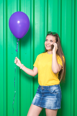Beautiful young woman talking on the mobile phone and holding helium balloon on green background.