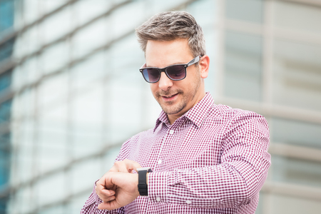 Close up portrait of businessman looking at his smart watch in front of office building. Reklamní fotografie