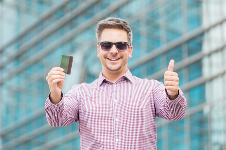 Portrait of young businessman holding credit card and showing thumbs up with office building in the background.
