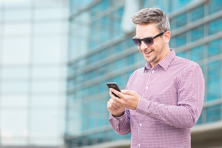 Businessman holding mobile phone with office building in the background. Space for copy.