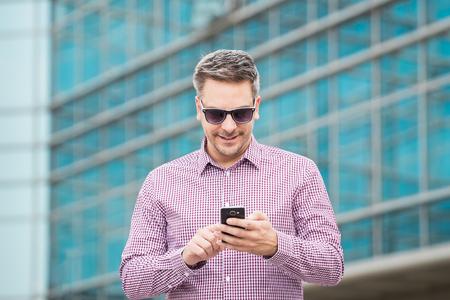 Portrait of fashionable businessman using smartphone outdoors. 版權商用圖片