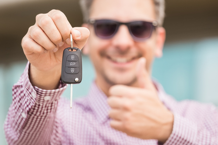 Close up portrait of man holding car key and showing thumbs up.