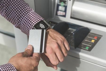 Close up of man using wireless payment system with credit card and smart watch next to atm. Reklamní fotografie