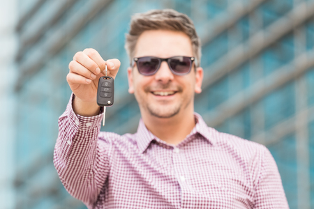 Portrait of man holding car keys with business building in the background.
