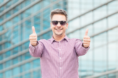 Happy executive in sunglasses showing thumbs up outdoors. Reklamní fotografie
