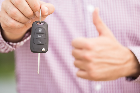 Close up of unrecognizable man in shirt holding car keys and showing thumbs up.