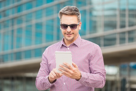 Portrait of businessman using digital tablet with office building in the background.
