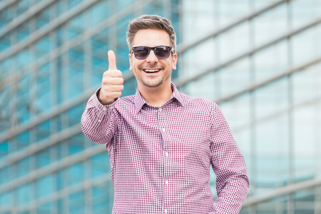 Portrait of cheerful businessman with thumbs up in front of business building.