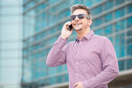 Handsome businessman talking on the cellphone with office building in the background. Space for copy.