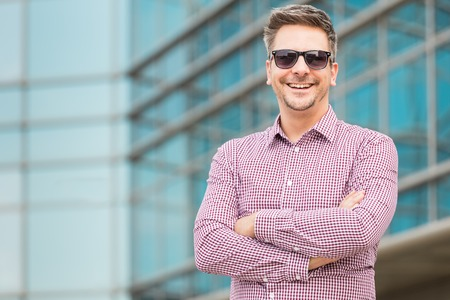 Portrait of young fashionable businessman with office building in the background, Space for copy.