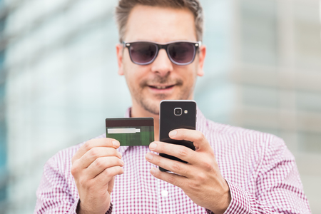Close up portrait of businessman paying online with his credit card on office building background. Reklamní fotografie