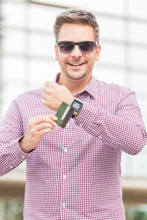 Man making payment by using smartwatch and debit card outdoors.