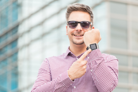 Businessman showing his blank screen smart watch. New technology concept.