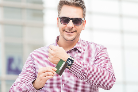 Businessman using wireless payment system with credit card and smart watch in front of business building. Reklamní fotografie