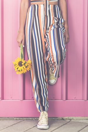 Hipster girl with sunflowers leaning against rose colored wall outdoors. Reklamní fotografie